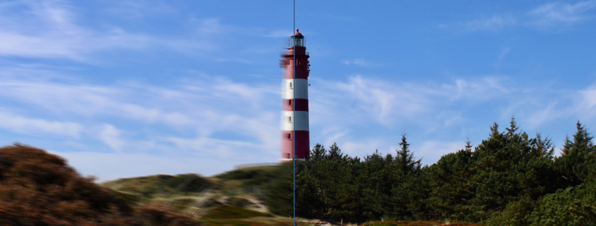 Der rot-weiß gestreifte Leuchtturm von Amrum in der Mitte, vor blauem Himmel mit einigen Wolken. Er steht auf einer Düne, drumherum Heide, Dünengras und Kiefernwald. Die linke Hälfte des Bildes ist verschwommen, die rechte scharf. Foto: Birte Vogel