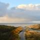 Zwei Wege in den Dünen: ein Bohlenweg links, ein Sandweg in der Mitte, beide führen runter zum Strand und zum Meer, die man im Hintergrund sieht. Darüber einige Wolken, eine regnet sich über dem Meer ab, und ganz oben hellblauer Himmel. Foto: Birte Vogel