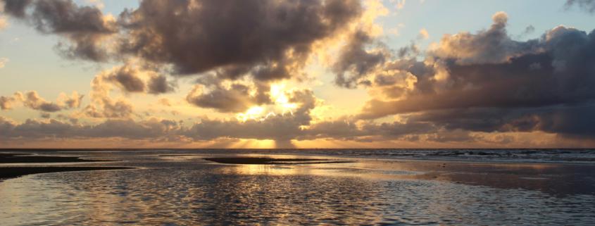 Sonnenuntergang am Meer: Die Priele sind vollgelaufen, nur ein bisschen Sand schaut noch raus, über dem Wasser Wolken, hinter denen die Sonne untergeht. Hinter einer längeren Wolke sieht man die Sonnenstrahlen hindurchkommen. Foto: Birte Vogel
