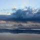Blick vom Strand aufs Meer, über dem eine breite Regenwolke hängt und sich abregnet. Sie spiegelt sich im Wasser auf dem Sand. Darüber hellblauer Himmel. (Foto: Birte Vogel)
