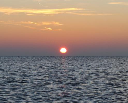 Sonnenuntergang am Meer, im Vordergrund ein leicht gewelltes, dunkelblaues Meer, darüber ein rötlich gelber Himmel mit wenigen goldfarbenen Wolkenschleiern, und in der Bildmitte die Sonne als rote Kugel. Foto: Birte Vogel