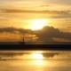 Sonnenuntergang am Meer, im Vordergrund aufgelaufenes Wasser, dahinter Strand, am Horizont das Meer, darüber Himmel mit Wolken, und alles in goldenes Licht getaucht (Foto: Birte Vogel)