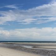 Im Vordergrund ein menschenleerer Strand, durchzogen von einem kleinen Pril, im Hintergrund dunkelblau das Meer, darüber ein blauer Himmel mit vielen weißen Wolken. Foto: Birte Vogel