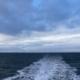 Im Vordergrund das dunkelblau-grau-braune Meer mit leichtem Wellengang, in dem eine Fähre eine Spur weißen Schaums hinter sich gelassen hat, der geradeaus von der Bildmitte Richtung Horizont läuft. Am Horizont Land (in diesem Fall eine Insel), darüber ein stark bewölkter Himmel in verschiedenen Blau- und Grautönen. (Foto: Birte Vogel)
