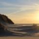 Links im Vordergrund Dünen, rechts erstreckt sich der Strand, am Horizont das Meer darüber eine gleißende Sonne kurz vorm Sonnenuntergang, noch hellgoldfarben. Foto: Birte Vogel