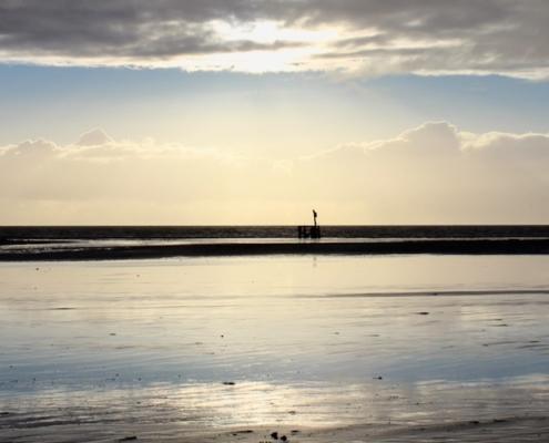 Blick vom Strand aufs Meer, im Vordergrund Wasser auf dem Strand, in dem sich die Wolken spiegeln, im Hintergrund das dunkle Meer, darüber Wolkenstreifen und blauer Himmel. Mittig steht eine dunkle Holzkonstruktion. (Foto: Birte Vogel)
