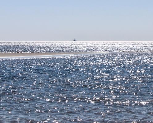 Ein ganz blaues Meer im Vordergrund, das zwar unruhig ist, aber nur kleine Wellenbewegungen zeigt. Von links kommt mittig eine kleine Sandbank ins Bild. Am Horizont ein Krabbenkutter. Der Himmel darüber hellblau. (Foto: Birte Vogel)