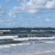 Wellen auf einer leuchtend dunkelblau-grünen Nordsee. Am Horizont die Insel Sylt. Darüber ein blauer Himmel mit einigen Schäfchenwolken. (Foto: Birte Vogel)