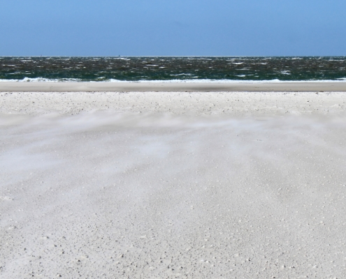 Weißer Sandstrand, über den der Sand vom dunkelgrünen, unruhigen Meer auf dich zugeweht wird. Darüber ein leuchtend blauer Himmel. (Foto: Birte Vogel)