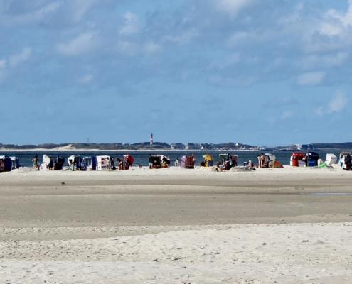 Im Vordergrund weißer Strand, in der Mitte eine große Anzahl bunter Strandkörbe, die in alle möglichen Richtungen stehen, am Horizont die Insel Sylt, darüber ein blauer Himmel mit einigen Wolken (Foto: Birte Vogel)