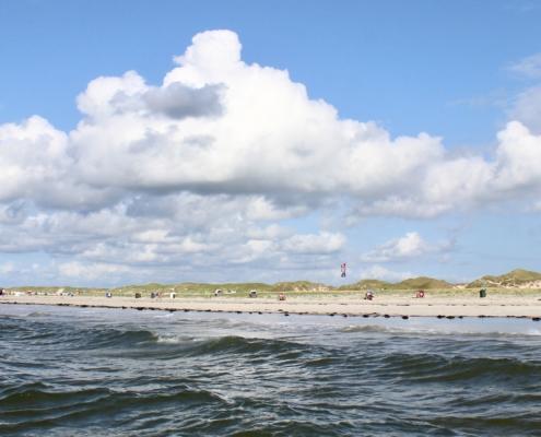 Im Vordergrund Meereswellen, dahinter ein Strand mit einigen bunten Strandkörben, dahinter ein breiter Dünengürtel. Darüber ein blauer Himmel mit einigen weißen und grauen Wolken. (Foto: Birte Vogel)