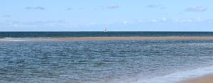 Im Vordergrund ein dunkelblaues Meer, in der Mitte, einmal quer von rechts nach links, eine noch feuchte Sandbank, dahinter am Horizont ein einsames Segelboot mit weiß-orangefarbenem Segel. Der Himmel ist hellblau mit wenigen kleinen Wolken. (Foto: Birte Vogel)