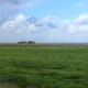 Im Vordergrund links ein Busch mit leuchtend dunkelroten Hagebutten, dahinter eine grüne Wiese, dahinter auf einer leichten Anhöhe ein Reetdachhaus, rechts davon die Nordsee, am Horizont die Insel Föhr. Der Himmel ist teils hellblau, teils ziehen Wolken von links auf. (Foto: Birte Vogel)